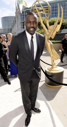 Idris Elba in a black shawl lapel tuxedo and skinny black long tie on the Emmys 2014 red carpet.