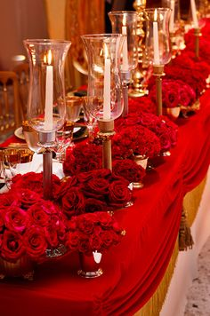 Countless red roses are arranged in mixed metallic vases and placed beside trumpet hurricanes for a regal feel.