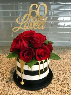 A beautiful black and white striped fondant cake with gold drip and red roses