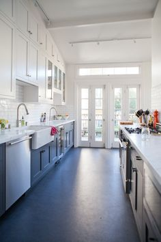 White upper cabinets, blue lower cabinets, light marble counters, dark gray Marmoleum flooring. + LOTS of natural light!
