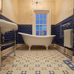 Arundel pattern in dover white blue and grey in a bathroom with blue and white artworks tiles on the wall