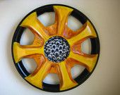 Reminds me of a sunflower.  This repurposed hubcap would look great in a garden.