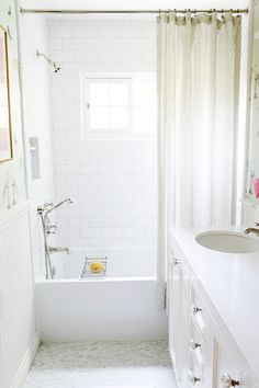 Sun drenched kids' bathroom features tub shower combo with fixed and adjustable shower heads adorning a subway tiled surround which frames a narrow window finished with a patterned beige shower curtain. The bathroom boasts beadboard wainscoting across from a white double vanity adorned with crystal pulls and a white counter with oval sink above marble mini brick tiled floors.