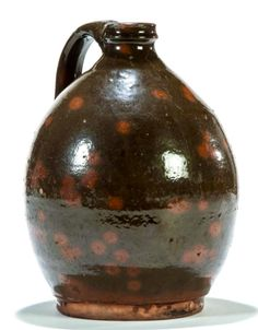 """Garth's 5/14/16 Lot 195.  Estimate: $ 600 - 800.  Realized: $ 960.   Description: AMERICAN REDWARE JUG.  Gonic, New Hampshire, ca. 1839-1885. Dark green with orange spots. Applied handle. Flaking. 9""""h. Condition Report: Glaze flakes on the surface and top edges. 2-3 rim flakes (mostly in the glaze), glaze flakes on the handle with an additional bruise to one side of the handle. Surface wear around the widest part of the jug."""