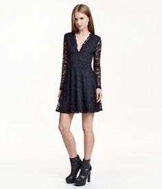Short lace dress with a circle skirt and long sleeves. Low-cut V-neck at front with scalloped trim. Lined with attached jersey liner dress.