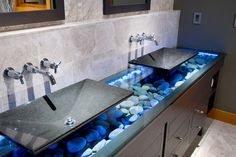 Very dramatic under-lit floating sinks over river rocks. This bathroom uses a plethora of beautiful textures and is super stylish!    Caption by Jenn Brown