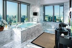 The suite'swhite-marbled bathroom features a Jacuzzi bathtub positioned next to the window overlooking the cityscape