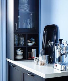 Kaffemaskin på smal IKEA-benkeplate. Veggskap med kopper, kaffe og glasstøy.