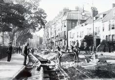 Laying the tram rails in Marlborough Place. Note the King and Queen Hotel, rebuilt in 1931 and old fashioned private houses adjoining. At this period Victoria Gardens were enclosed within a high iron fence.