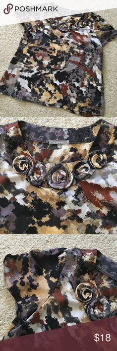 Beautiful blouse with rosettes Multi-colored pattern matches so many outfits, gray, black, brown, tan, gold, and purple. Gorgeous rosette details at neck. Size XL approximately a 14R. NY Collection Tops Blouses
