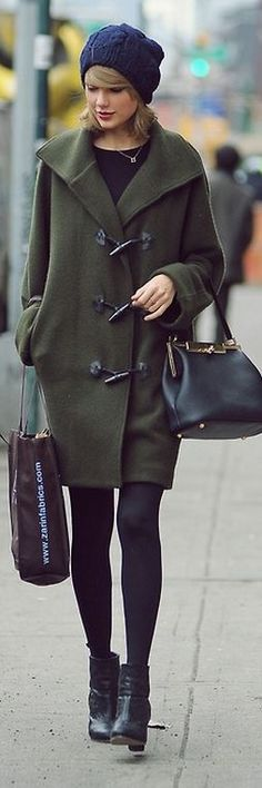 Taylor Swift in a green coat, black handbag, and leather ankle booties