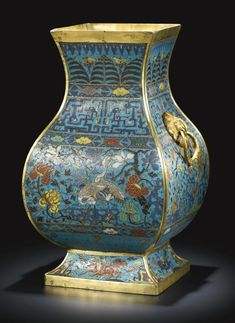 A CLOISONNÉ ENAMEL 'CRANE AND PEACOCK' VASE, FANGHU QING DYNASTY, QIANLONG PERIOD of square section, the pear-shaped body rising from a spreading foot to a flared rim, the shoulders flanked by a pair of gilt-bronze animal mask handles, brightly decorated against a turquoise ground to each facet of the body with alternate scenes of pairs of cranes and peacocks in lush garden settings, framed above by pairs of confronted kui dragons, encircled at the neck by upright lappets and clouds, the…