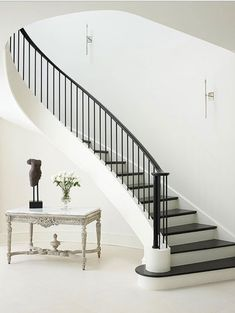 Staircase Design Ideas Flowing Staircase – Flowing down like the train of an elegant gown, this staircase creates a dramatic style statement. The dark wood treads and metal balustrade lend contrast to the otherwise all-white foyer. Modern Stair Railing, Wrought Iron Stair Railing, Stair Handrail, Modern Stairs, Railing Design, Staircase Design, Railing Ideas, Staircase Ideas, Staircase Remodel