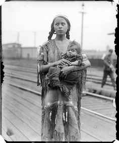 Native American woman with child at train station circa 1930