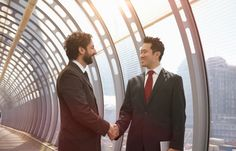 Businessmen shaking hands in a futuristic tunnel