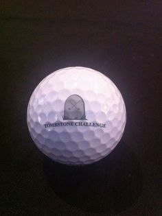 """Logo golf ball. Titleist PRO V1 in near mint condition with the logo """"TOMBSTONE CHALLENGE"""" with a pic of a tomstone."""