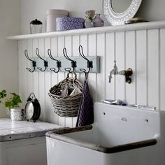 Laundry space. High shelf above top edge of white wainscoting. Vintage hooks and deep white sink.