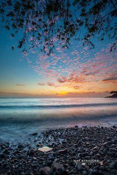 Puesta de sol de una playa rocosa. Foto por Nat Stravers.