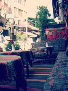 Istanbul. A breezy bohemian cafe... great idea to cover some tables with tapestries and textiles like this.