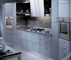 look of modern steel oven and counter in metal cabinets. Scavolini Italian Kitchen w/ glass cabinet doors.