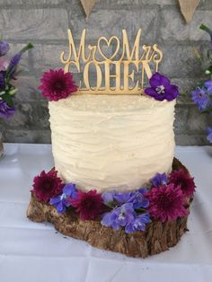 Elegant rustic wedding cake featured on timber tree board with wooden topper