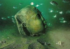 A serene face of a statue underwater in Alexandria.