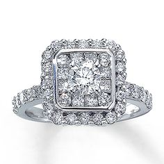 A remarkable round diamond takes center stage in this eye-catching ring for her. A cluster of round and princess-cut diamonds delivers scintillating sparkle around the center stone. Stunning round diamonds decorate the 14K white gold band in brilliance. This fine jewelry ring has a total diamond weight of 1 3/4 carats. Available online while supplies last.