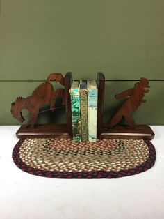 This is a unique set of vintage bookends. They are a cowboy and his horse with a rope made of wire that looks like it stretches between the two parts. They seem to be handmade with light etched details on the horse and rider (shown in picture). It has a decidedly Western feel and