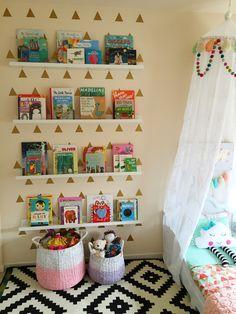 Interior design by Maya Ostrander. Toddler bed, bed canopy, felt balls, tassels, book ledges, library, kids books, roman shades, polka dots, cloud pillow, custom toddler bedding, flamingo print, bunny lamp (PB Teen), Ikea rug.
