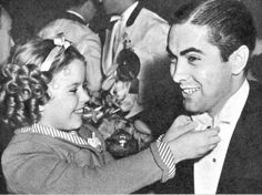 Shirley Temple helps a delighted Tyrone Power with his tie