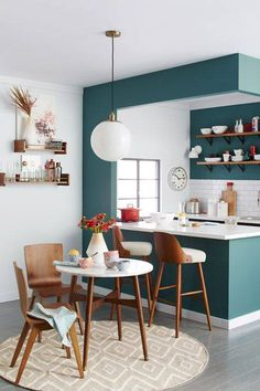 A deep teal tone helps to divide this eating and cooking space. An accent wall has the power to create zones in your small space.
