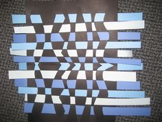 Fold a piece of paper in half and cut wavy or angled lines, leaving a little space before cutting to the end.  Then weave in different colored strips of paper.  Versatile uses - scrapbooking background, framed photo background, framed art, kids craft, etc.