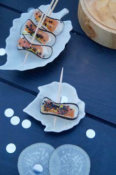 Des petites bouchées apéritives composées de très fines tranches de radis noir sur lesquelles reposent des morceaux de saumon fumé parsemé de sésame et de zeste de citron vert