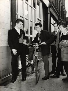 """Boys wearing Edwardian style clothes at the """"Teen Canteen"""" at Elephant & Castle, South London, July 1955 - note the unusually long sideburns of the Teddy Boy with the double-breasted waistcoat for the period."""