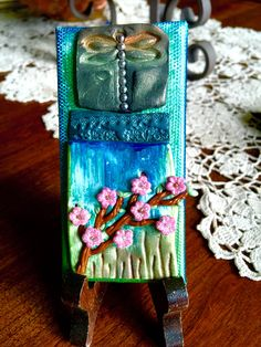 Polymer clay. On canvas. Using stamps and flower embellishments. Painted with viva gold colors of blues and green. Dragonfly impressed with stamp.