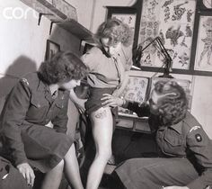 Women's Royal Army Corps member showing new tattoo on her leg to fellow enlistees.