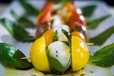 Caprese Bites - basil leaves, mozzarella balls, tomatoes, cracked pepper and olive oil.
