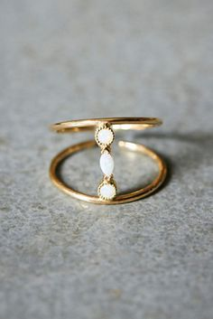 "Katie Diamond Adelaide Ring. ""14k gold and opal ring, featuring fluted, beveled opal stones connecting two delicate adjustable bands."" 