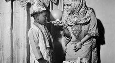 A woman feeds her son the first bite of his birthday cake. Kiembe Samaki, January 2013 Photo by: Ania Gruca