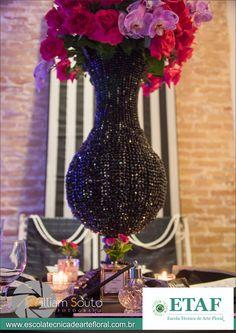 Mesa dos convidados com Spray com lança perfume e frase da Coco Chanel e flores pink.