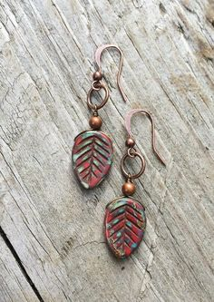 "Small, rustic red Czech glass leaves with antiqued copper. Approx 1.5"" in length and light weight."