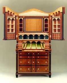 This collector's cabinet is also a desk with an infinity model. Made in amboyna, lacewood, satinwood, holly and Indian rosewood. Made by Andrew Varah.
