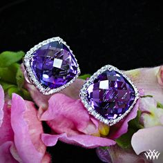 White Gold Amethyst and Diamond Earrings. Stunningly beautiful, these Amethyst and Diamond Earrings are the ultimate in glamour. Two incredible cushion cut amethysts are surrounded by 56 sparkling Round Brilliant Diamond Melee.