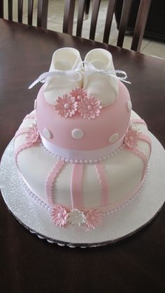 Baby shower cake - cake is covered in an ivory & baby pink fondant, and topped with gumpaste booties & daisies. Misschien leuk als dooptaart :-) Torta Baby Shower, Baby Shower Kuchen, Tortas Baby Shower Niña, Baby Shower Pasta, Beautiful Cakes, Amazing Cakes, Fondant Cakes, Cupcake Cakes, Fondant Bow