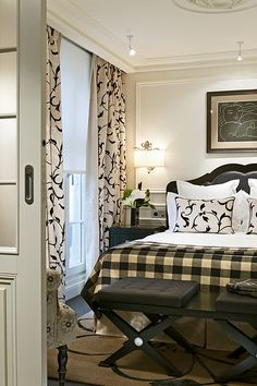 Black and white is a winner here. I love how they extended the crown molding to make a sort of cornice for the draperies. That's attention to detail. The headboard having wood trim around the black leather upholstery is very attractive & its shape softens the room. Well lit & nicely done.