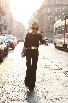 Black & Gold in Milan - versatile look.    I love this effortless look from how the clothes fit the model, the width of the  accent gold pieces yet the slender lengthy necklace, the hair, glasses, then down to the flair of the pants.