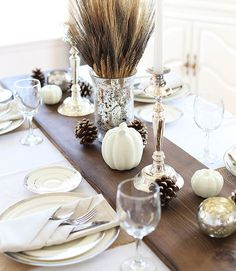 Metallic candle holders, frosted pinecones, and white pumpkins stand out against a dark stained wood table runner. See more at Blooming Homestead.   - CountryLiving.com
