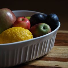 Gray day light. A still life of fall fruit: Italian plums, all sorts of apples and one lemon for good measure.