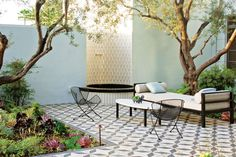 Beneath the olive trees, a Heath Ceramics-tiled water feature with Plain Air furniture and striking encaustic Granada Tile underfoot.