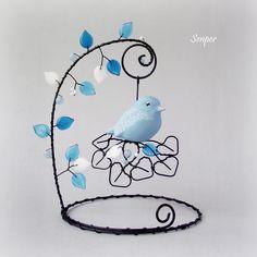 Na+zamrzlé+větvičce+Drátovaná+dekorace z+černého+žíhaného+drátu+dozdobená+modrými+a+bílými skleněnými+korálky.+Na+větvičce+je+zavěsen keramický+ptáček+od+Bohdy krásně+domalován+od+AMY. +Rozměry+:+průměr+podstavce je+13+cm+a+výška+celé dekorace cca+18,5+cm+(+měřeno+s+přesahem+lístečků+).+Ptáček+se+při+pohybu+se+stojánkem+i+s+větvičkou pohupuje+...